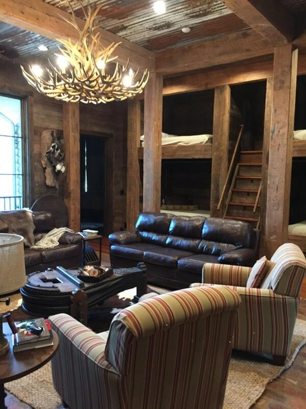 Hunting lodge bunk room with reclaimed beams, siding and rolling tin roof